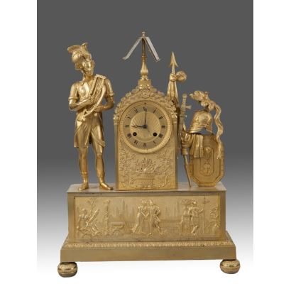 Reloj de sobremesa en bronce dorado al oro fino, a modo de alegoría musical  representa a un músico con arpa sobre peana rectangular con escena galante narrada en relieve, a su lado un conjunto de armaduras clásicas. Francia Siglo XIX. Medidas: 47x34cm