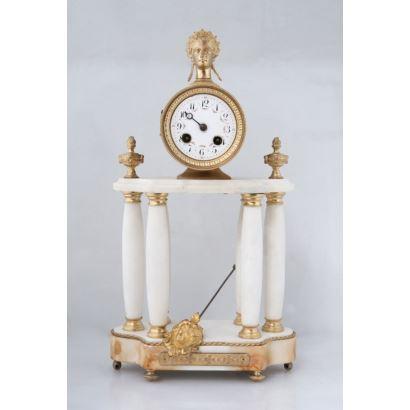 Reloj de sobremesa IMPERIO con péndulo,  en mármol blanco con aplicaciones de bronce dorado, tiene cuatro columnas que sostienen un friso que alberga la esfera rematada con una cabeza clásica. Medidas: 44x23x11cm.