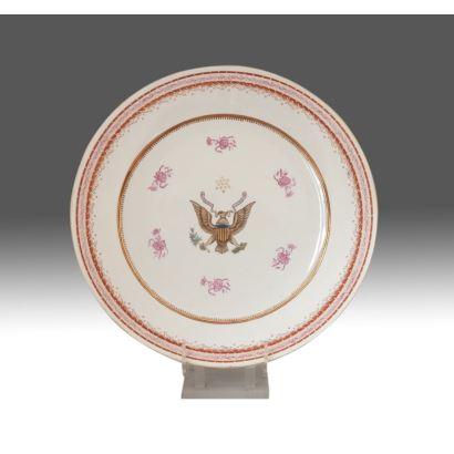 Plato en porcelana policromada de COMPAÑÍA DE INDIAS, s.XIX. Con decoración de águila entre motivos florales rosas. Diámetro: 47cm.