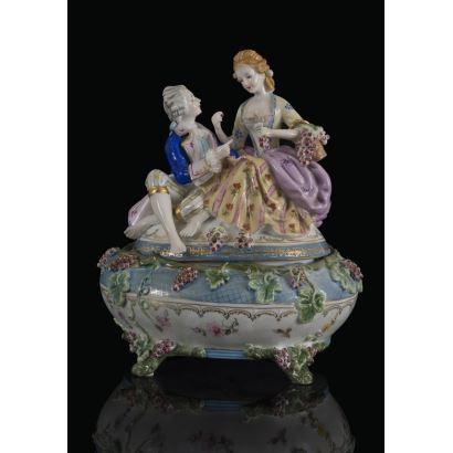 Bombonera en porcelana policromada, con excepcional tapa que alberga una escena galante dieciochesca protagonizada por un caballero y una dama con racimos de uvas. Marca en base. 33x26x25cm.