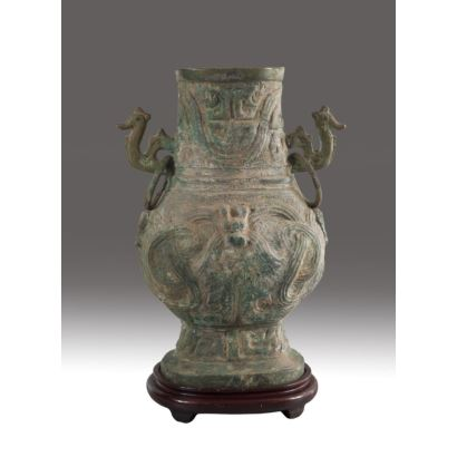 Chinese bronze vase, archaic style, circa 1900. Geometric decoration on the body and handles in animal form. With wooden base. Measures with base: 43 x 29 x 17 cm. Measures without stand: 38 x 29 x 14 cm.