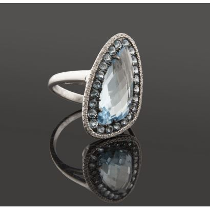 Original sortija de oro blanco, con gran topacio azul facetado orlado por zafiros azules y brillantes (0,30cts).