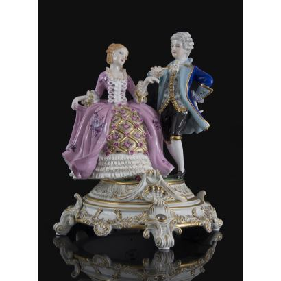 Magnificent figure of rococo taste in polychrome porcelain, represents a man and a woman elegantly dressed in eighteenth-century fashion on a base with rich golden details. 32x27x27cm