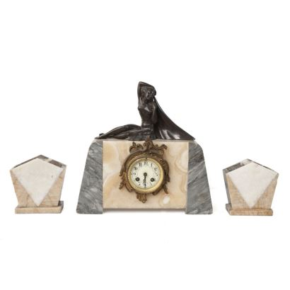 French Art Deco table clock with trim, from the house AD MOUGIN Deux Mèdailles, made of marble of various colors and topped by a lady figure in bronze. Early 20th century Measures: 36x36x16cm.