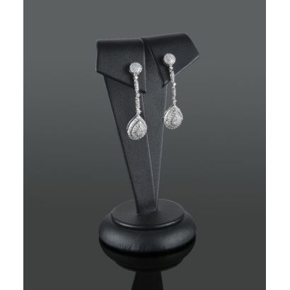 Long earrings in white gold and covered with diamonds that add 1ct, with rosette in closure that hangs an articulated strip that holds tear.
