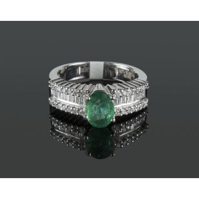 White gold ring with an oval-cut emerald set in a claw, flanked by a row of princess-size diamonds and two rows of diamonds totaling 0.63cts. Color H. Purity SI.