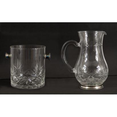 Lote formado por una jarra, una cubitera y una licorera con tapa realizados en fino cristal tallado y plata de ley. Licorera: 29x10cm, cubitera: 13x12cm, jarra: 16x13cm.