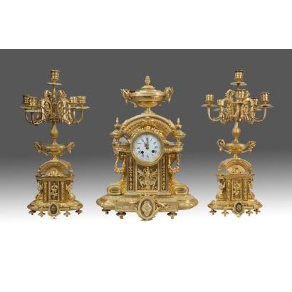 Large table clock with candle holders, all in fine gold bronze, with rich decoration of cups and rolls. Signed in sphere. Clock: 53x40cm Candlesticks: 56x20cm