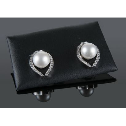 Elegant white gold earrings with 10.6mm Australian pearl surrounded by row-shaped diamonds totaling 0.37cts. Omega type closure.