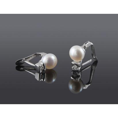 Pendientes en oro blanco, albergan una perla y un brillante en la parte inferior, suman 0,04cts. Especial para niñas.