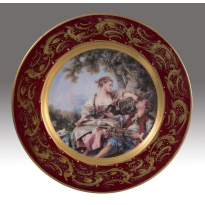 Plato en porcelana de Limoges realizado en Egipto, con decoración de gusto rococó y borde en tono granate con motivos dorados pintados. Marca en reverso: