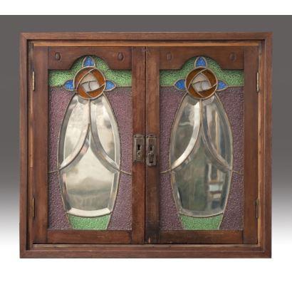Espejo enmarcado con doble puerta de vidriera decorada con motivos geométricos y vegetales.  Primera mitad siglo XX. Medidas: 61x68cm.