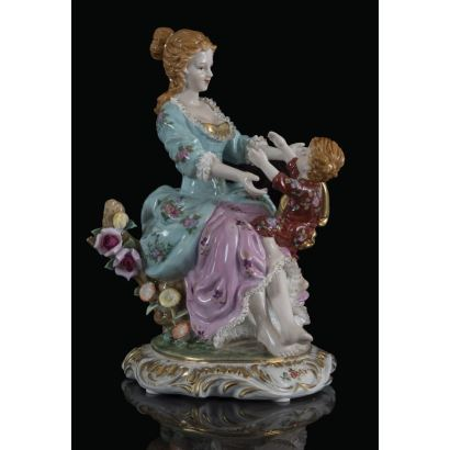 Bonita figura de porcelana policromada y dorada, en ella una mujer juega con un niño sentado sobre su regazo en entorno boscoso, ambos a la moda dieciochesca. Marca en base. 32x18x18cm.