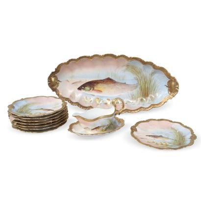Servicio de ocho platos, fuente oval y salsera, en porcelana policromada a mano con motivos de peces y dorado en bordes, en porcelana de LIMOGES COMTE D'ARTOIS. SIGLO XIX.