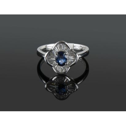 White gold ring with an oval central sapphire set in a claw cut by princess-size diamonds totaling 0.46cts, within a polylobulated structure.