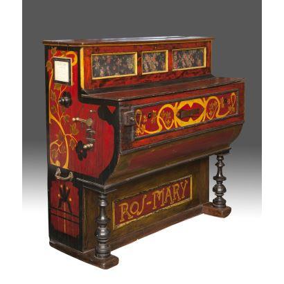 Organillo de principios del siglo XX realizado en madera policromada, cuenta con nota de las piezas que alberga, con decoración floral sobre fondo rojo. Medidas: 124x130x59cm.