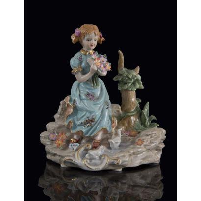 Bonita figura de porcelana policromada, en ella una niña sentada sobre unas rocas sujeta un ramo de flores. Marca en base.  20x18x10cm.