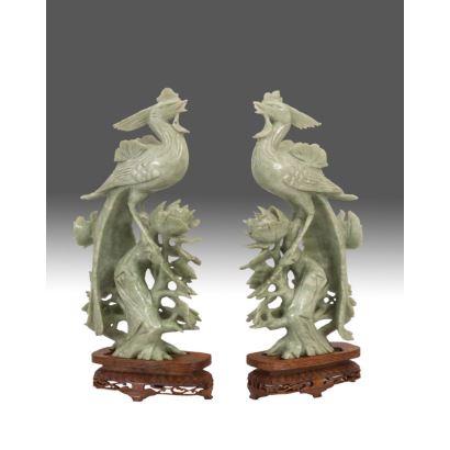 Bella pareja de tallas realizadas en jade verde sobre peana de madera, representan a una pareja de ave fénix sobre motivos florales calados. Medidas: 31x16cm.