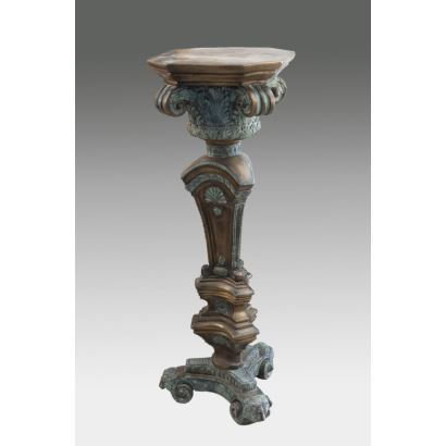 Pedestal in patinated bronze, the upper body has the shape of a capital with acanthus and scrolls, under this the pyramidal shaft decorated with scallops, is supported on a foot with three volutes and lion heads. Measurements: 116x40x40cm.