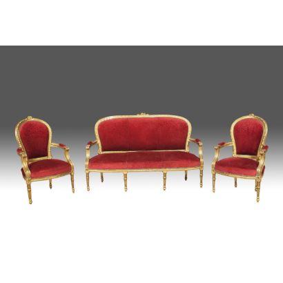 Conjunto de sofá y pareja de sillones, en madera tallada y dorada, con tapicería en color rojo, elegantes patas acanaladas, estilo Luis XVI. s. XX.