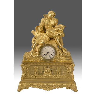 Beautiful Empire-style clock with sculptural scene at the top, where we observe a gallant scene on the dial. Base with low relief scenes. 52x18x40cm