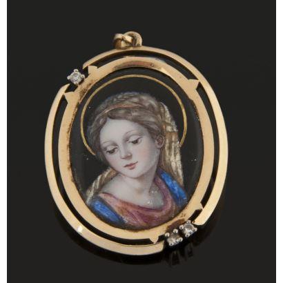 Bonito colgante oval en oro amarillo e imagen de la Virgen realizada en esmalte, con tres brillantes que suman 0,15cts. Largo: 4cm.