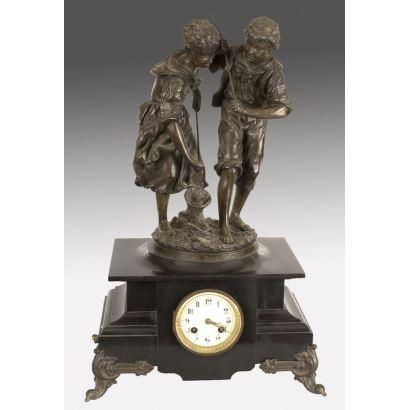 Relojes. Reloj de sobremesa con bonita decoración sobre peana en la que contemplamos a una pareja de niños jugando con una red realizados en bronce. ss.XIX-XX.
