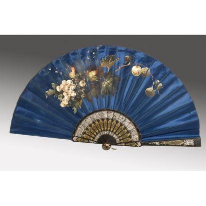 Magnífico abanico realizado en seda azul y pintado a mano con una bella decoración frutal. 35x5cm.