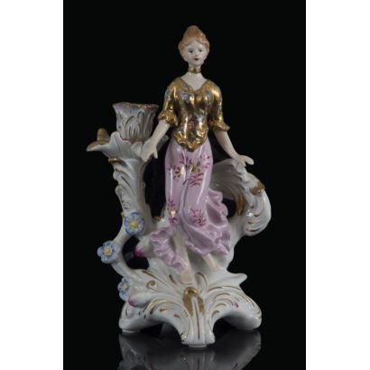 Original candelero en porcelana policromada, con figura de dama de gusto modernista en bulto redondo entre original brazo de roleo. Marca en base. 29x15x15cm.