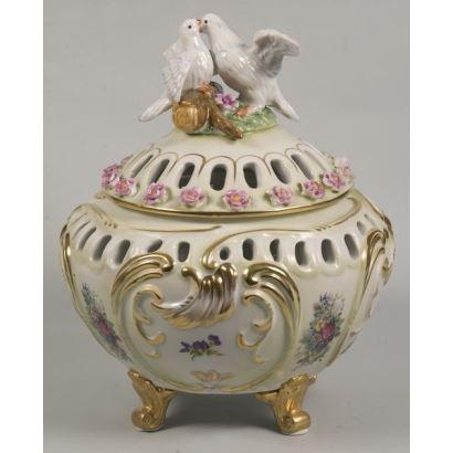 Bellísima bombonera en porcelana esmaltada donde encontramos decoración en relieve formando roleos dorados rematado por dos palomas en la tapa. 23cm de alturax18cm