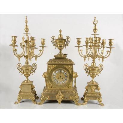 Magnífico reloj S.XIX francés de sobremesa con guarnición de dos candelabros a juego en bronce sobredorado de cinco brazos. El reloj se corona con un trofeo y flanquea con dos mascarones leoninos. 63x35x26cm reloj/72x17cm candelabros.