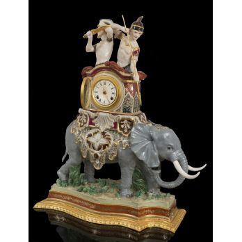 Magnífico reloj de sobremesa en porcelana policromada del s.XX, representa a una pareja de soldados romanos a lomos de un elefante que alberga la esfera, con gran colorido. Medidas: 88x59x26cm.