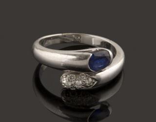 Sortija de oro blanco con original diseño rematado en los extremos por nueve brillantes y una piedra azul oval. Brillantes: 0,27cts. Peso: 5,2g. Diámetro: 17mm.
