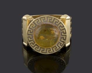 Magnífica sortija de oro amarillo, decorada por una piedra circular amarilla en cabujón orldada por grecas. 6,7g.
