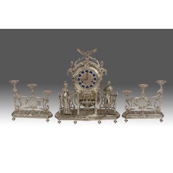 Elegante reloj de sobremesa plateado con guarnición de candelabros, la pieza cuenta con péndulo y decoración de personajes vestidos a la moda decimonónica, los candelabros  de tres luces se alzan sobre balaustre. Estado en marcha.