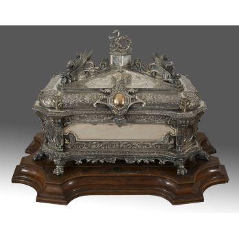 Gran urna de plata cincelada y relevada, decorada con motivos vegetales sobre fondo matizado, acantos anillados y grifos alados. Sobre patas de garra. Firmada Bacariza