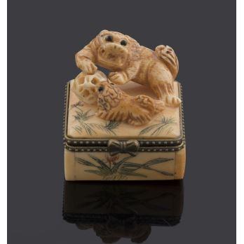 Cajita cuadrada en hueso, decorada en tapa con guardián de Fo con pata sobre bola. Medidas: 4,5x4x5cm.