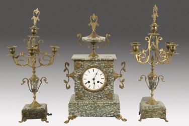 Magnífico reloj de sobremesa con guanición de candelabros, realizado en mármol de color verde jaspeado y apliques en bronce dorado.