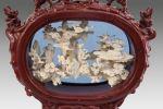 Objetos. Grupo escultórico chino realizado en símil de marfil (resina roja y blanca), se trata de un grupo de deidades femeninas entre motivos vegetales enmarcado dentro de estructura oval con elefantes. Medidas: 40x47cm.