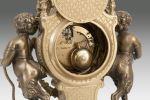 Relojes. Reloj de sobremesa estilo Luis XVI, cuenta con guarnición de candelabros en mármol verde jaspeado  y bronce dorado, con decoración de niños fauno. Reloj con forma de lira. Alto: 62cm.