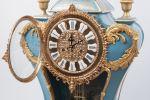 Relojes. Reloj de sobremesa realizado en porcelana policromada en azul, presenta delicada decoración floral en laterales y apliques en bronce dorado que forman numerosas rocallas, está rematado en copa clásica. Medidas: 110x53x35cm.